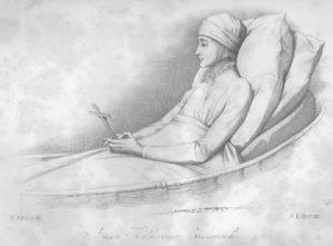Anna Katharina sitzt, an zwei dicken Kissen angelehnt, im Bett, der Kopf ist verbunden, sie hält und betrachtet ein Kruzifix, das sie in der Hand hält