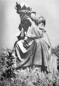 Die Muttergottes von La Salette, wie sie den Hirtenkindern erschienen ist, sitzt, den Kopf geneigt und mit beiden Händen das Gesicht bedeckt, weinend auf einem Stein; sie trägt ein Diadem mit Rosen berankt