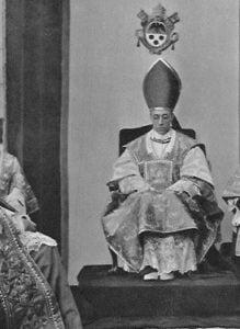 Papst Pius XII. sitzt in seinen päpstlichen Gewändern auf seinem Papststuhl, über ihm das päpstliche Wappen, die Hände hat er auf den Beinen liegen, er hat die Augen geschlossen.